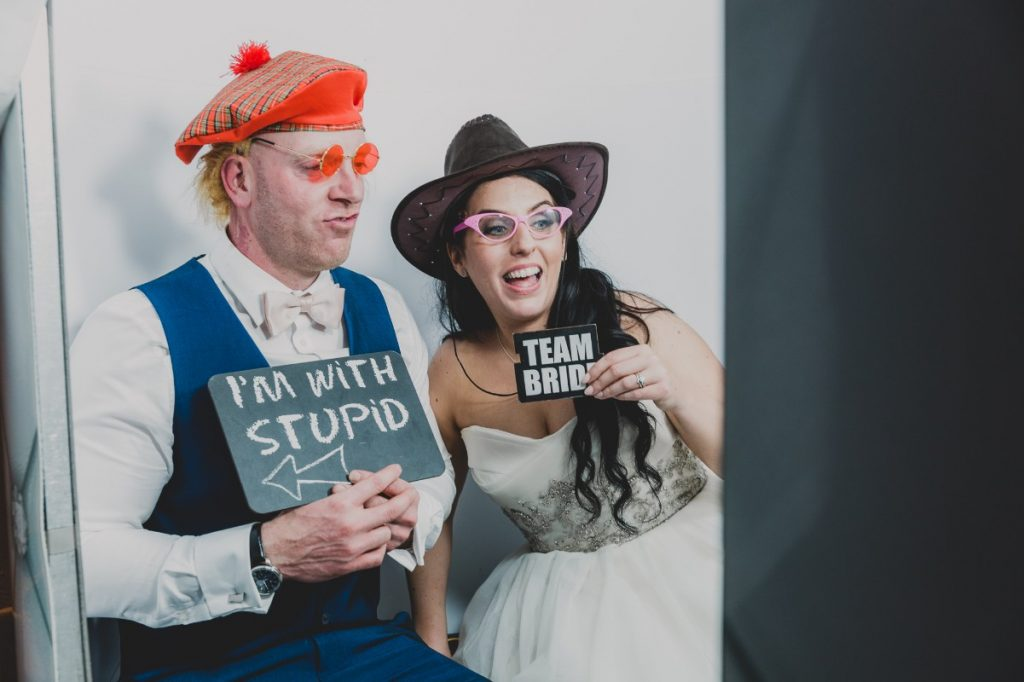 husband and wife in a photo booth holding props
